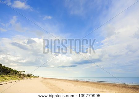 View of beach vegetation sea and sky with clouds