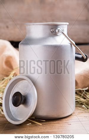 Milk can on wooden surface. Dry hay in the background. Life depends on ecology. Keep the level of calcium.