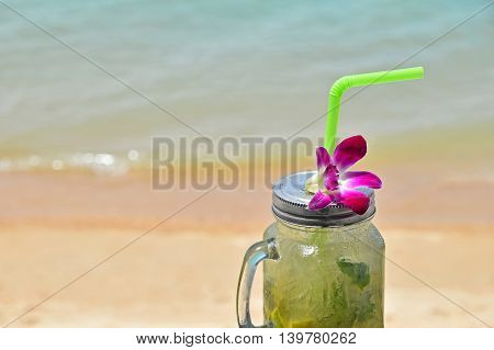 Big Glass Of Mojito With Orchid Flower On Beach