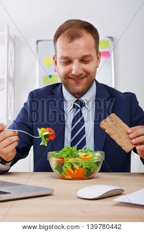 Man has healthy business lunch in modern office interior. Young handsome businessman at working place, looking at plate with vegetable salad in bowl, diet and eating right concept.