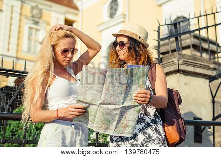Two attractive woman tourists looking at the map in city. Vacation concept. Summer vacation.