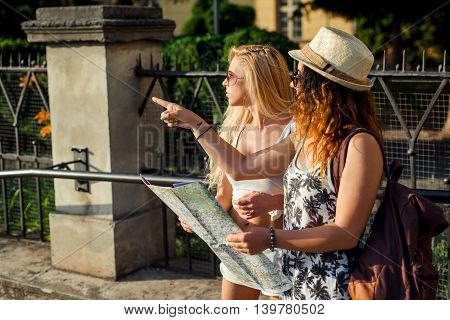 Two attractive woman tourists are pointing out the location. Vacation concept. Summer vacation.