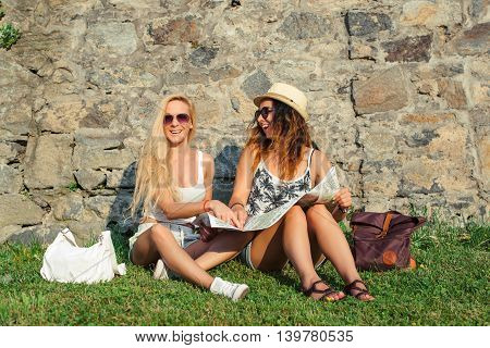 Two attractive woman tourists traveling on holidays in city smiling happy. Girls with city map in search of attractions. Summer vacation.