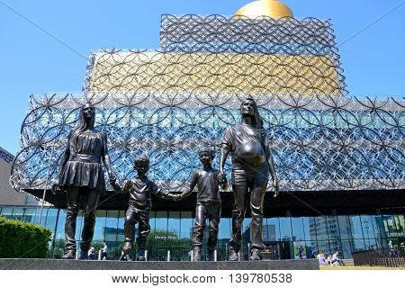 BIRMINGHAM, UNITED KINGDOM - JUNE 6, 2016 - The Library of Birmingham with A Real Birmingham Family statue in the foreground in Centenary Square Birmingham England UK Western Europe, June 6, 2016.