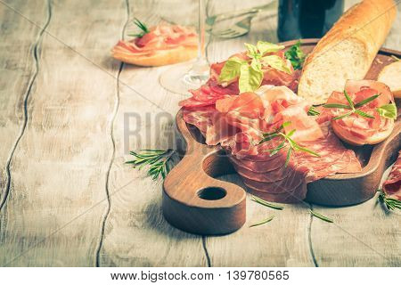 Concept of italian food with red wine, baguette and prosciutto on cutting board