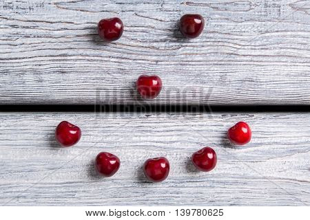 Smiley made of cherries. Red fruit on wooden surface. Make your immunity stronger. Summer welcomes you.