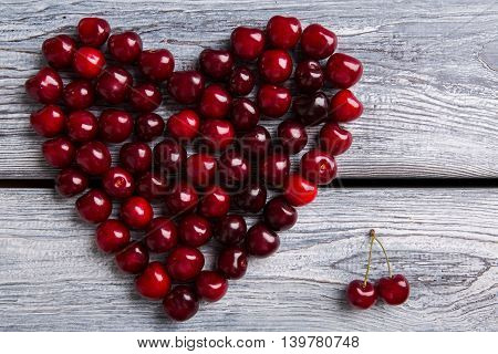 Heart made of dark cherries. Red fruit on wooden background. Summer sends love. Particles of art.