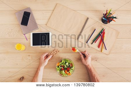 Business lunch at working place. Businessman in office. Hands of eating man. Healthy, diet food, vegetable salad with apple and juice. Notebook, tablet and pencils. Top view, flat lay