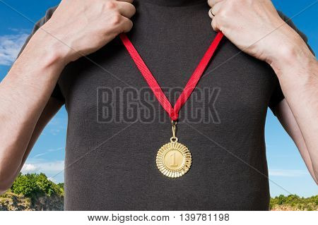 Champion Or Winner Is Putting Golden Medal On His Chest.