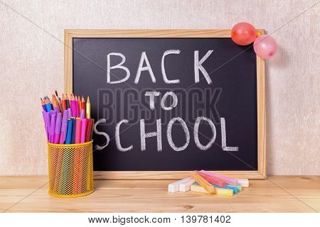 Education Concept With Text Back To School Is Written In Chalkboard, Chalks, Pen Holder, Balloons An