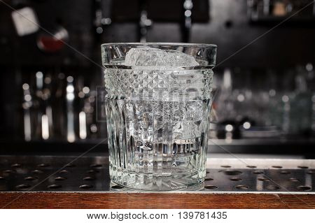 glass with ice on the bar bottles on background