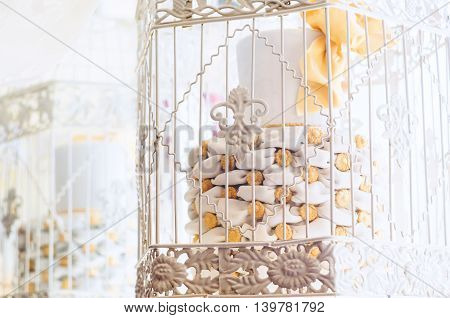 An artificial cake in a white cage.