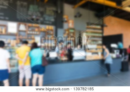 view people in front of counter inside busy coffee shop