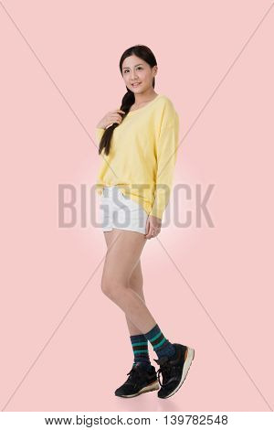 Attractive young woman of Asian standing, full length portrait isolated