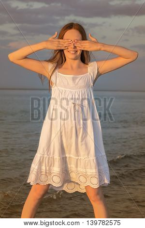 Portrait of a girl on the beach at sunset against the evening sky. Girl stands in the water eyes closed hands. Photo toned
