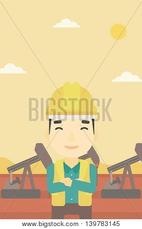An asian oil worker in uniform and helmet. An oil worker with crossed arms. An oil worker standing on a background of pump jack. Vector flat design illustration. Vertical layout.