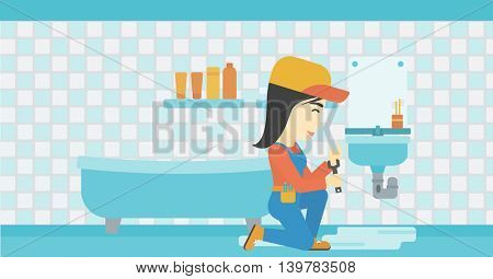 An asian female plumber sitting in a bathroom and repairing sink pipe. Plumber with wrench repairing a broken sink in bathroom. Horizontal layout.
