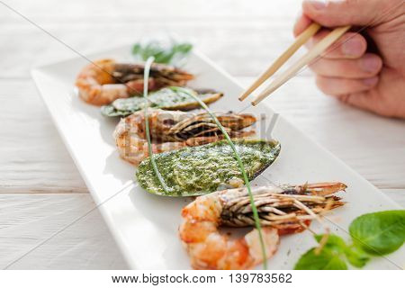 Seafood eating with chopsticks, close-up. Dining at asian restaurant with special cutlery