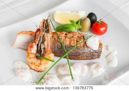 Grilled salmon and shrimp with cream sauce on white plate. Traditional mediterranean prepared seafood