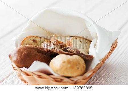 Basket with fresh hot bread on white wooden background, close-up. Organic crusty bakery products