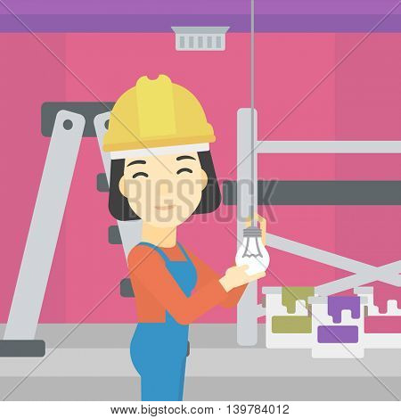 An asian female electrician twisting a light bulb. An electrician installing light in an apartment. Electrician changing light bulb. Vector flat design illustration. Square layout.