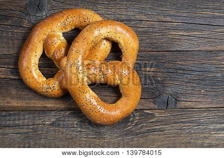 Pretzels with poppy seeds on wooden background top view