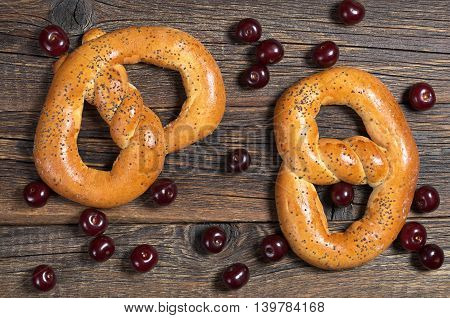 Pretzels with poppy seeds and cherry on wooden background top view