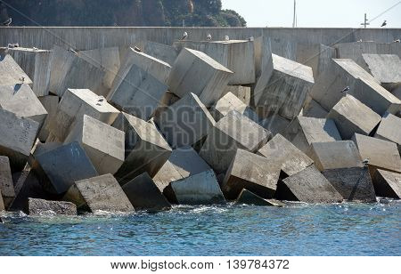 Concrete wall of breakwater with shaped cubic armour units at entrance of Blanes port Catalonia Spain.