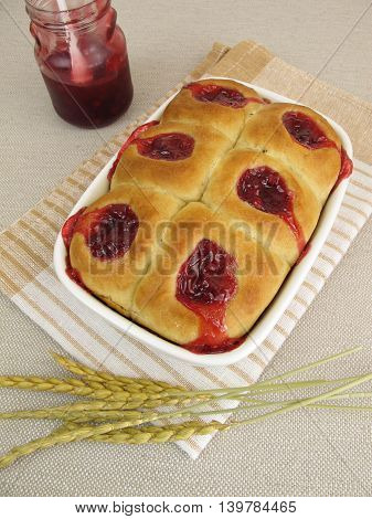 Sweet buns with lingonberry jam in baking pan