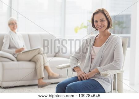 Portrait of smiling woman with her therapist at home