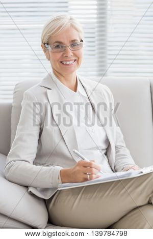 Portrait of smiling therapist with notes on sofa in office
