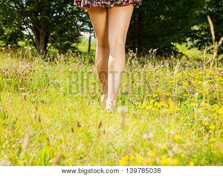 young girl going away barefoot on the grass on sunny summer day. legs closeup