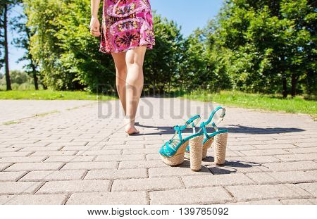 green shoes standing on sidewalk and female legs going away closeup