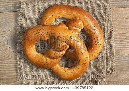 Tasty pretzels with poppy seeds on sackcloth on wooden table top view