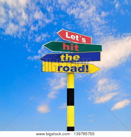 Sign post with four arrows of diffirent colors and directions and text - Let s hit the road on a blue sky background.