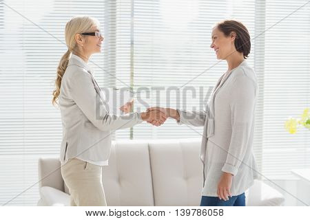 Smiling woman and therapist shaking hands at home