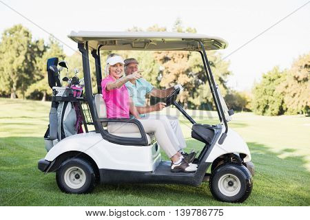 Happy mature woman pointing while sitting by man in golf buggy