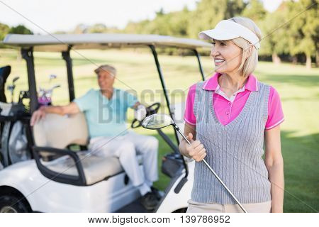 Happy mature woman holding golf club while standing by man