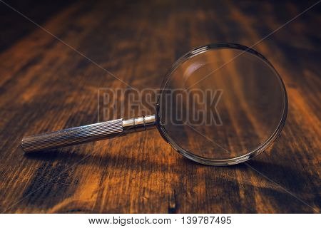 Loupe magnifying glass on wooden desk concept of searching and investigating