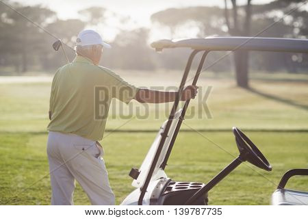 Rear view of mature man standing by golf buggy on field during sunny day