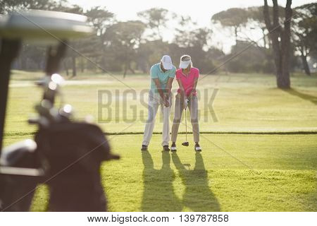 Full length of man teaching woman to play golf while standing on field