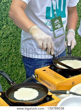 MONCHEGORSK, RUSSIA - JULY 2016: Master class on baking pancakes in city park on city-wide event dedicated to professional holiday
