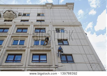 RUSSIA MOSCOW - JUNE 18 2015: Team of construction climbing workers reconstructing the facade of building in Moscow