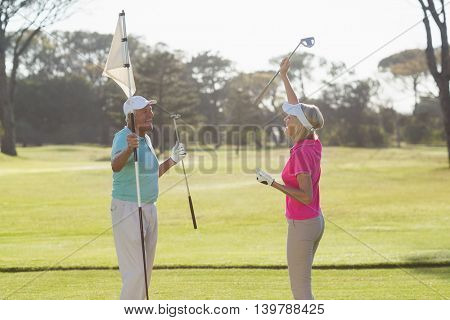 Happy mature golf player couple carrying flag while standing on field