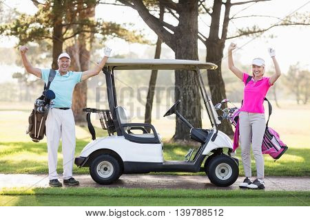 Portrait of smiling mature golfer couple with arms raised while standing on field