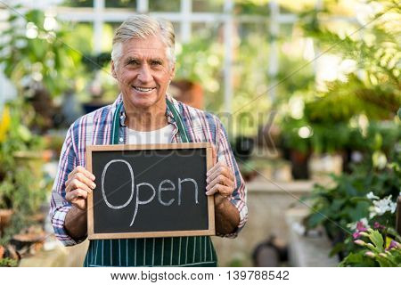 Portrait of mature owner holding open sign placard at greenhouse