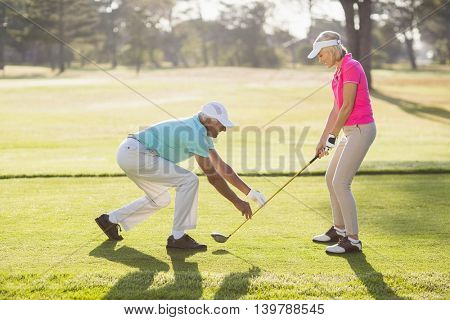 Side view of mature male teaching woman to play golf