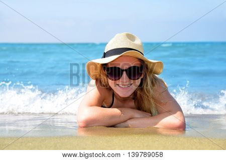 Caucasian girl with hat lying on the beach. Summer vacation by the sea.