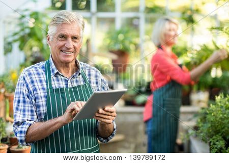 Portrait of senior man using digital tablet while woman working in background at greenhouse