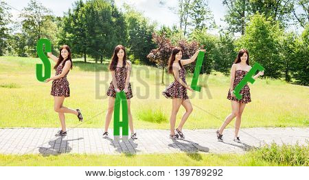four young pretty smiling girls holding letters with the word sale outdoor on sunny summer day
